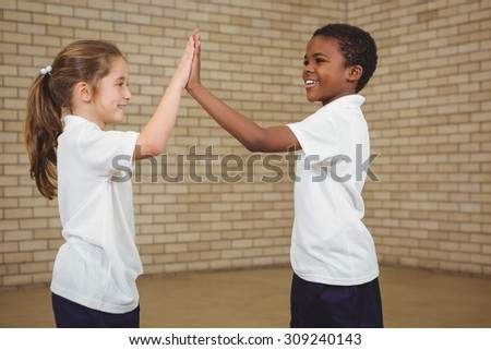 Happy pupils giving each other a high five at the elementary school - stock photo