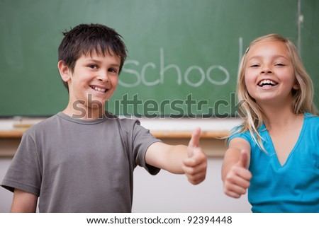 Happy pupils posing with the thumb up in a classroom - stock photo