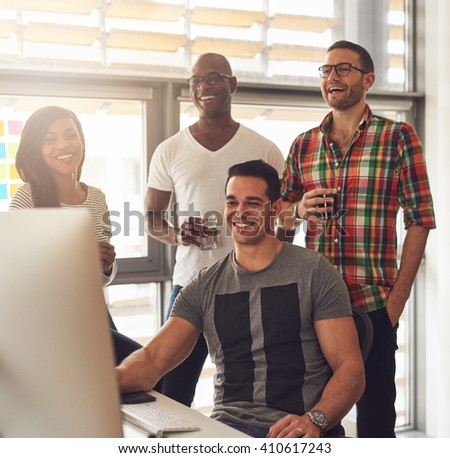 Happy quartet of Black, Hispanic and Caucasian young adults at desk smiling and laughing while looking at computer monitor with drinks in hand - stock photo