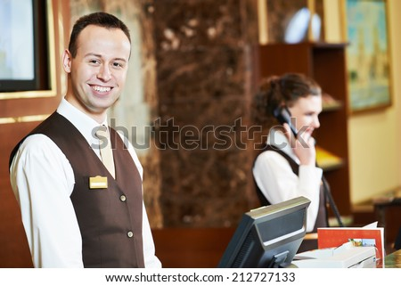 Happy receptionist worker standing at hotel counter - stock photo