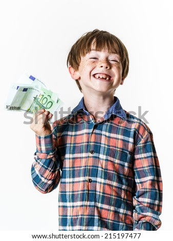 Happy red-haired boy with money in his hand - stock photo