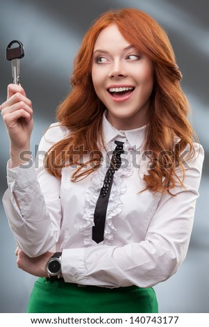 happy red haired woman holding big key - stock photo