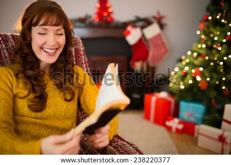 Happy redhead reading on the armchair at christmas at home in the living room - stock photo