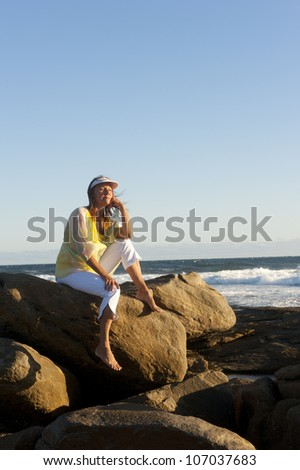 Happy relaxed and attractive looking mature woman sitting on a rock at the ocean contemplating, daydreaming, isolated with se and blue sky as background and copy space. - stock photo