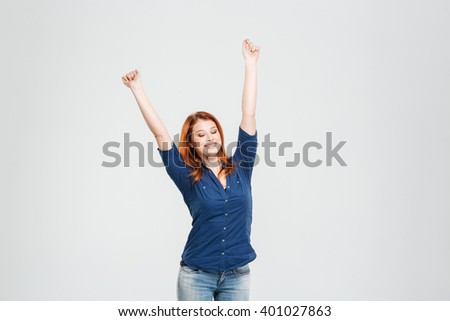 Happy relaxed attractive redhead young woman with eyes closed and raised hands stretching over white background - stock photo