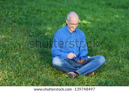 Happy relaxed businessman using digital tablet while sitting on grass at park - stock photo
