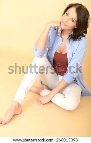 Happy Relaxed Contented  Attractive Beautiful Young Woman Sitting on the Floor Wearing a Blue Shirt and White Jeans - stock photo