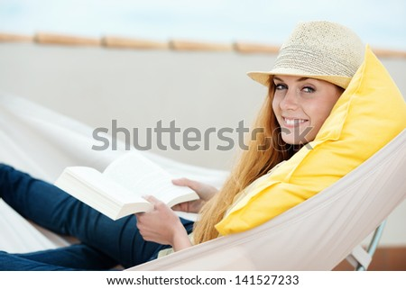 Happy relaxed young woman reading book in the hammock - stock photo