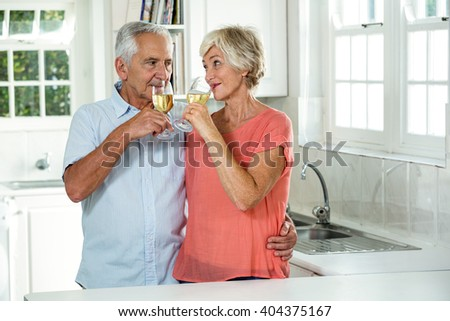 Happy retired couple drinking white wine while standing in kitchen - stock photo