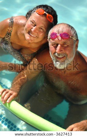 Happy retired couple having fun in the swimming pool in bright matching goggles - stock photo