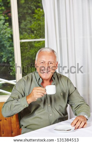 Happy retired man drinking a cup of coffee in a rest home - stock photo