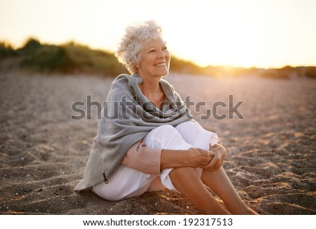 Happy retired woman wearing shawl sitting relaxed on sand at the beach. Senior caucasian woman sitting on the beach outdoors - stock photo