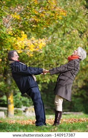 Happy romantic couple holding hands and pulling each other - stock photo