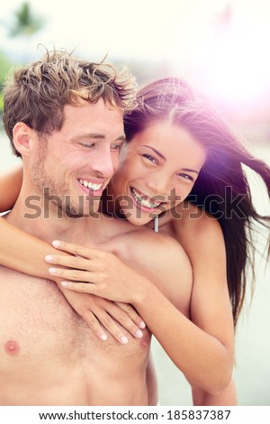 Happy romantic couple lovers on beach honeymoon having playful fun together during summer beach holidays. Cheerful young multiracial couple, Asian woman and Caucasian man in their twenties. - stock photo
