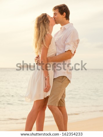Happy romantic couple on the beach at sunset embracing each other. Man and woman in love watching the sun set into ocean - stock photo