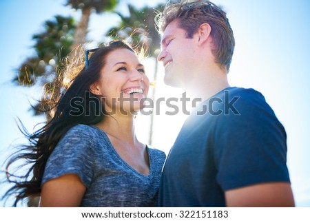 happy romantic couple outside on sunny day with palm trees shot with lens flare and selective focus - stock photo