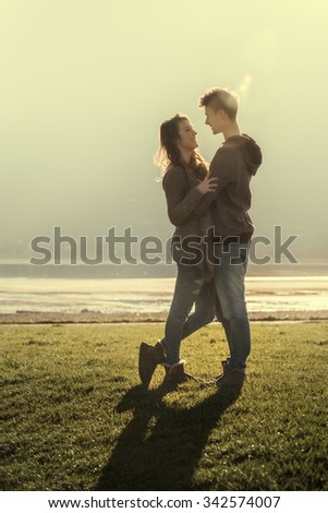 Happy romantic loving couple at the lake hugging and staring at each other, love and relationships concept - stock photo