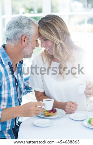 Happy romantic mature couple holding coffee cup at table in restaurant - stock photo