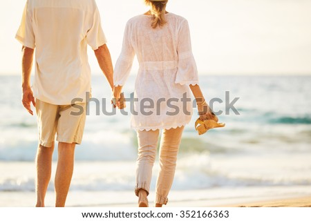 Happy Romantic Middle Aged Couple Enjoying Beautiful Sunset Walk on the Beach Holding Hands - stock photo