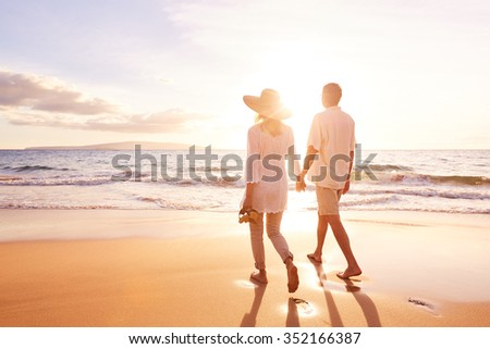 Happy Romantic Middle Aged Couple Enjoying Beautiful Sunset Walk on the Beach. Travel Vacation Retirement Lifestyle Concept - stock photo