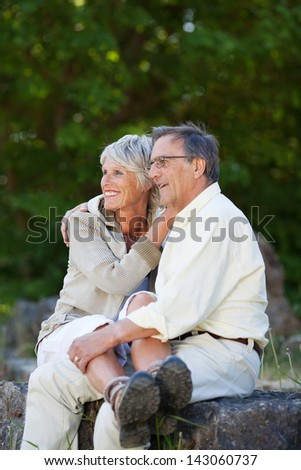 Happy romantic senior couple looking away while embracing in park - stock photo