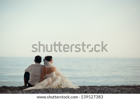 happy romantic wedding couple in love, men and women in white wedding dress sitting on the beach and look at the horizon - stock photo