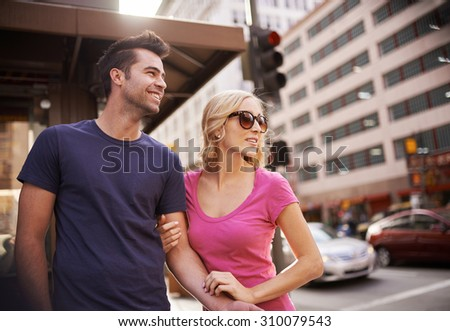happy romantic young couple waiting to cross street in down town LA - stock photo