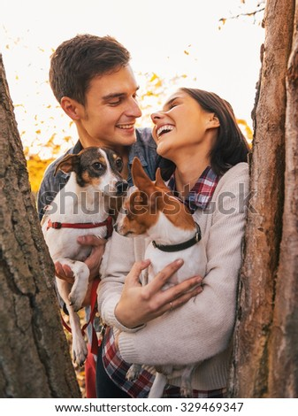 Happy romantic young couple with two dogs in autumn park between trees and smiling each other - stock photo