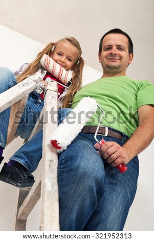 Happy room painters on a ladder - father and little girl smiling - stock photo
