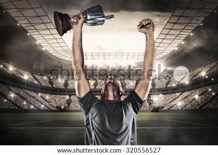 Happy rugby player holding trophy against large football stadium with lights - stock photo