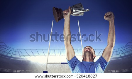 Happy rugby player holding trophy against rugby stadium - stock photo