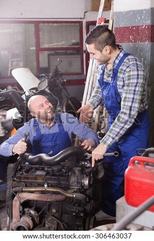 happy russian car mechanics in coveralls working at carshop - stock photo