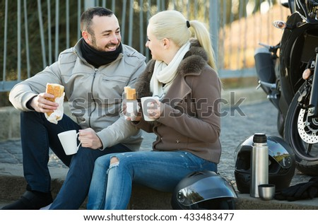 happy russian couple posing near motor bike with sandwitches and coffee - stock photo