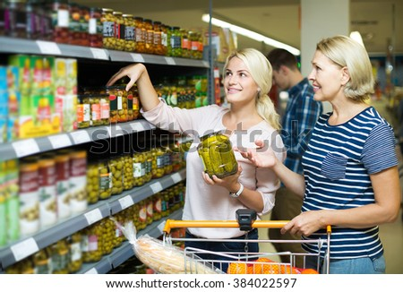 happy russian girl and mature woman purchasing canned food at supermarket - stock photo