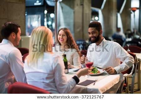 happy russian middle class people enjoying food in cafe terrace - stock photo