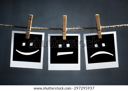 Happy, sad and neutral emoticons on instant print transfer photographs hanging on a clothesline - stock photo