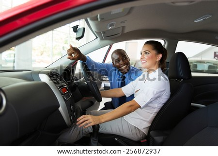 happy salesman explaining car features to young female customer - stock photo