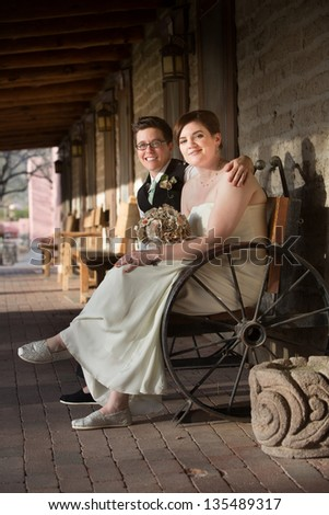 Happy same sex couple in wedding on antique bench - stock photo