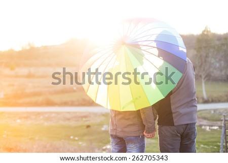 Happy same sex couple under rainbow umbrella - stock photo