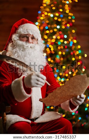 Happy Santa answering Christmas letter - stock photo