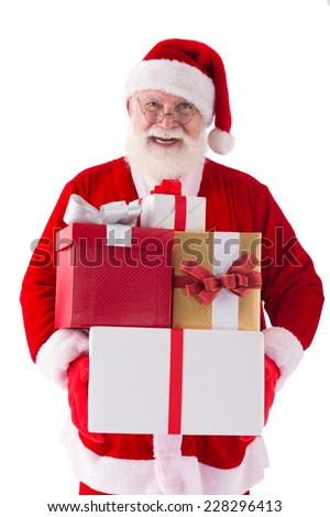 Happy Santa Claus holding a pile of gift boxes - stock photo