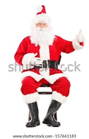 Happy Santa claus sitting on a wooden chair and giving a thumb up isolated on white background - stock photo