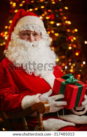Happy Santa Claus with package looking at camera on background of sparkling firtree - stock photo