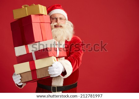 Happy Santa Claus with xmas presents looking at camera - stock photo