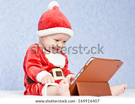happy santa helper baby boy with digital tablet on a blue background - stock photo