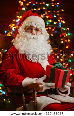 Happy Santa with box looking at camera while sitting by sparkling firtree - stock photo