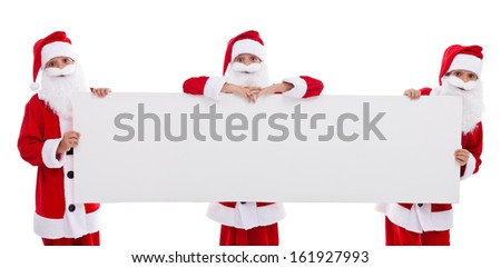 Happy santas holding blank banner with copy space - isolated - stock photo