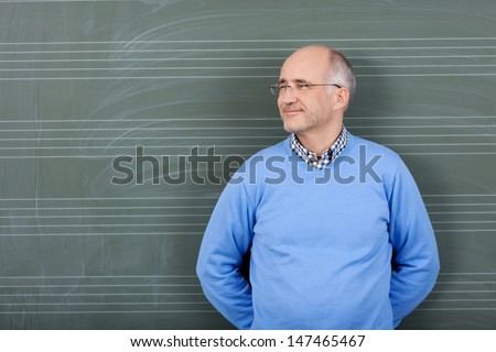Happy satisfied male teacher standing with his hands behind his back and a pleased smile against a blank green blackboard - stock photo