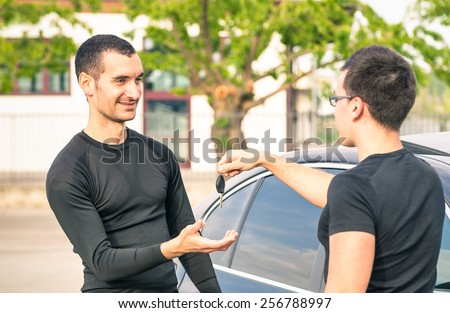 Happy satisfied young man receiving car keys after second hand sale - Concept business transport trade of modern luxury vehicles - Car rental assistance and customer care - Focus on man at left - stock photo
