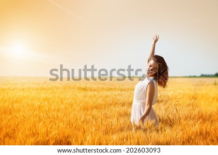 Happy, satisfied young woman with arms outstretched standing in the wheat field.Copy space, sunset, flare light, summer season  - stock photo